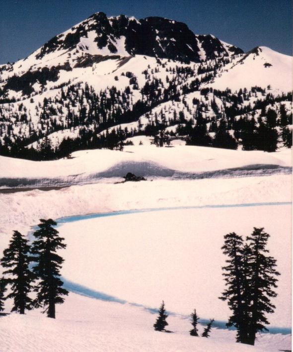 Frozen Lake Helen, road cut, and Brokeoff Mountain beyond