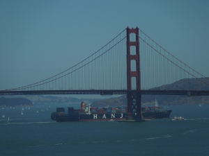 A massive container ship cruises under the Golden Gate Bridge